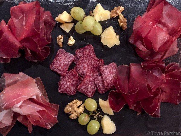 Verschiedene getrocknete Fleischspezialitäten aus der Schweiz angerichtet auf einer Schieferplatte für ein Apéro
